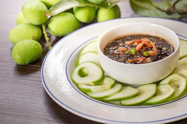 Saure und süße soße der rohen mangos mischen garnelenpaste, thailändischer snack im weißen teller