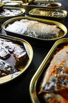 Saury, makrele, sprotten, sardinen, sardinen, tintenfisch, thunfisch, fischkonserven in blechdosen. offen und geschlossen über schwarzem schieferhintergrund seitenansicht neue weitwinkelvertikale.