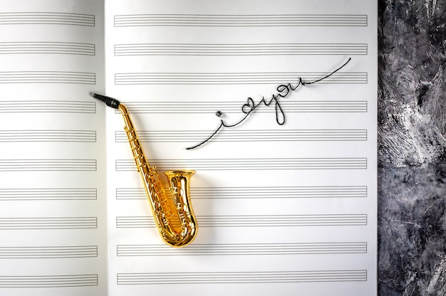 Saxophon auf hintergrund des musiknotizbuches mit den wörtern