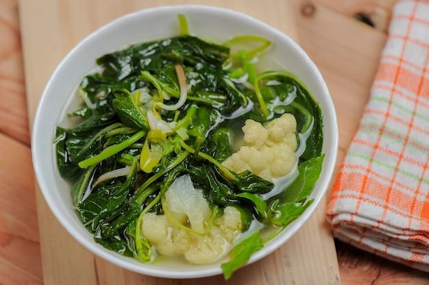 Sayur bening bayam oder spinat klare suppe mit brokkoli in einer weißen schüssel und holz