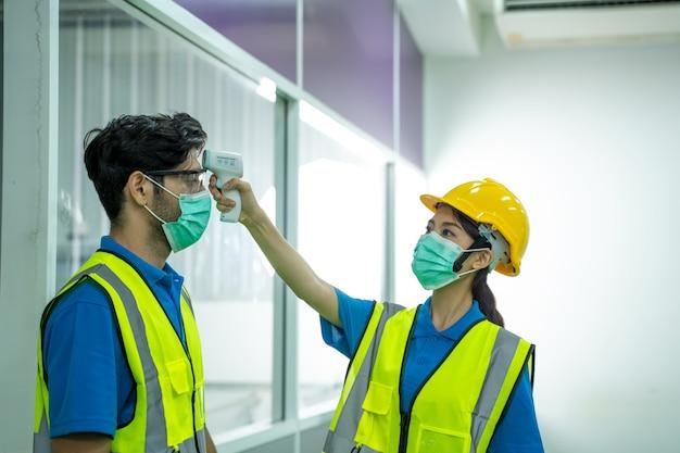 Scan-temperatur des industriearbeiters vor der arbeit im werk