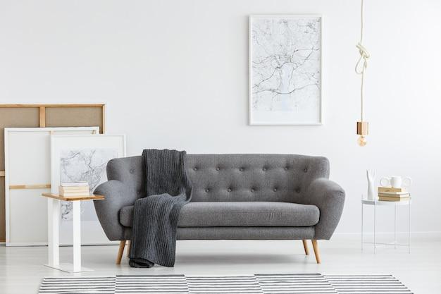 Scandi-wohnzimmereinrichtung mit grauem, großem sofa in der mitte und modernem bild an der wand