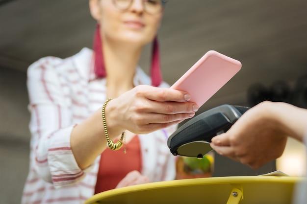 Scannen. progressiver besucher eines cafés, das ein modernes smartphone in der hand hält und den code scannt, während er ohne kreditkarte am terminal bezahlt