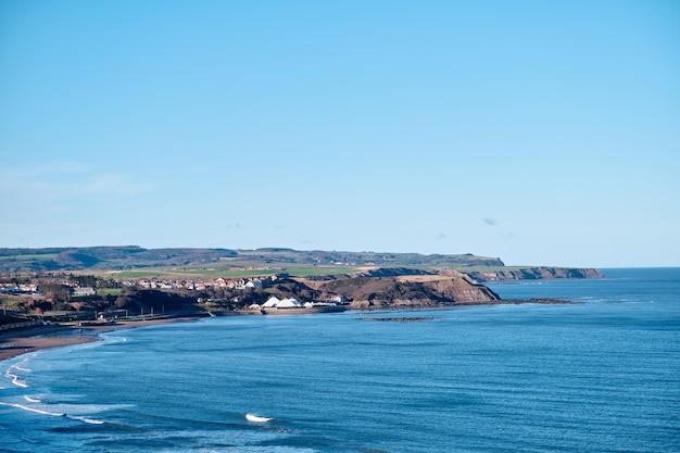 Scarborough küste unter einem klaren blauen himmel während des tages