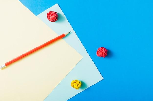 Scarp bleistift mit zerknittertes papier auf kartenpapier über blauem hintergrund