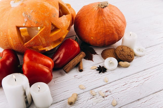 Scarry halloween-kürbisstand auf tabelle mit kerzen, zimt, rotem pfeffer und nüssen