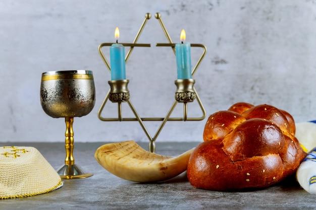 Schabbat mit challahbrot auf kerzen eines holztischs und einer tasse wein.