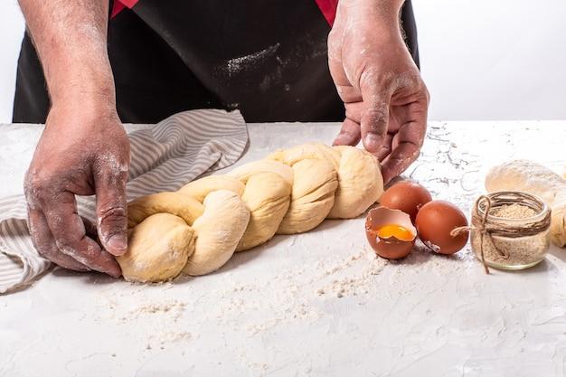 Schabbat- oder schabath-konzept. bäcker, der traditionelles jüdisches challa-brot macht