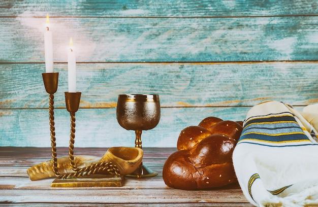 Schabbat-tischkerzen und eine tasse wein mit bedecktem challa-brot,