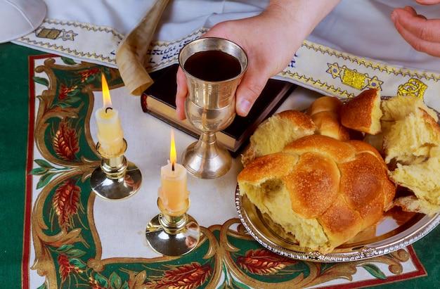 Schabbat-vorabend-tisch mit offenem challa-brot, sabbat-kerzen