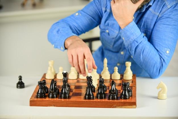 Schach spielen. intellektuelles hobby. figuren auf holzschachbrett. über den nächsten schritt nachdenken. taktik ist zu wissen, was zu tun ist. entwicklungslogiken. schach spielen lernen. schachunterricht. strategiekonzept.