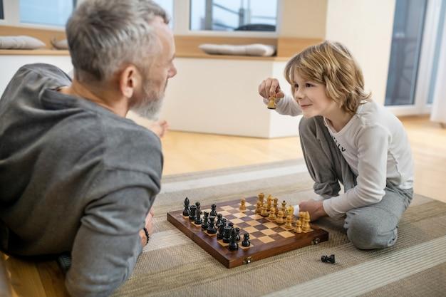 Schach spielen. vater und sohn spielen schach und sehen involviert aus