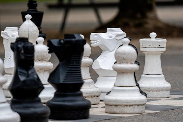 Schachbrett im freien mit großen plastikstücken. riesenschach im freien in der zone des öffentlichen bereichs. schließen sie große straßenschachstücke im park