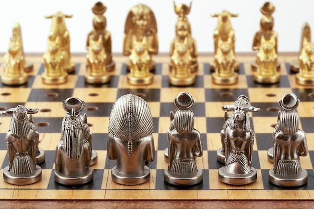 Schachbrett mit platzierten schachfiguren stilisiert als ägyptische götter