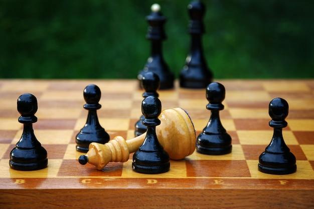 Schachendspiel - besiegte weiße schachkönigin, umgeben von schwarzen bauern