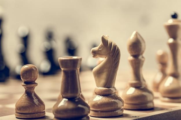 Schachfiguren auf dem brett im selektiven fokus der unschärfe