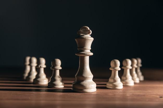 Schachfiguren auf dem tisch an einer dunklen wand