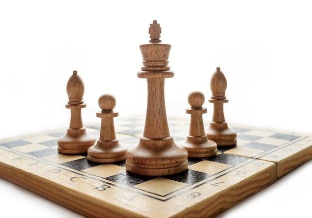 Schachfiguren auf einem brett auf weißem hintergrund mit kopienraum.