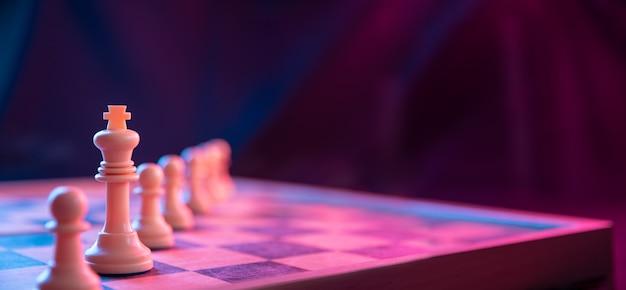 Schachfiguren auf einem schachbrett auf einem dunklen hintergrund, der in neonrosa-blauen farben geschossen wird. die figur eines schachspiels.
