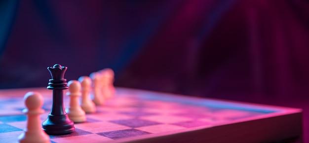 Schachfiguren auf einem schachbrett auf einem dunklen hintergrund schossen in neonrosa-blauen farben.