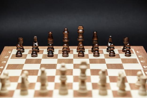 Schachfiguren auf einem schachbrett gegen eine dunkle wand. neue partei, konzept der erfolgsstrategie und die richtige wahl