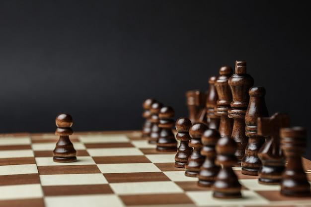 Schachfiguren auf einem schachbrett gegen eine dunkle wand. schwarze figuren stehen in einer reihe, das konzept der erfolgsstrategie und die richtige wahl