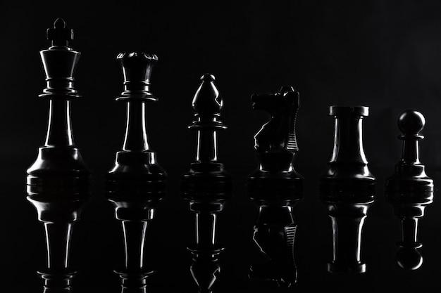Schachfiguren auf hintergrundabschluß des dunklen schwarzen oben