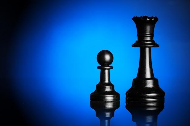 Schachfiguren auf schwarz mit blauer hintergrundbeleuchtung