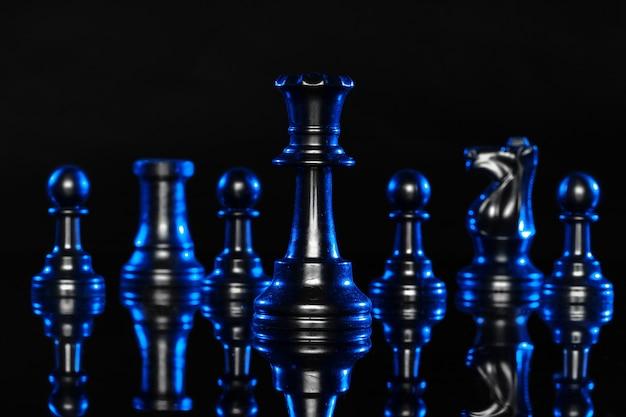 Schachfiguren auf schwarzem hintergrund mit blauer hintergrundbeleuchtung
