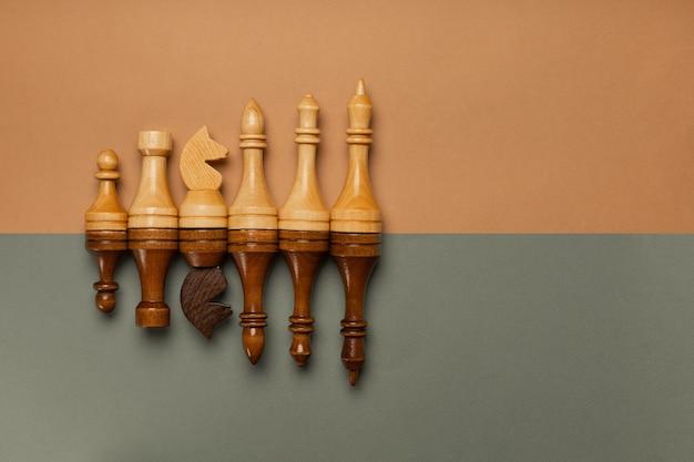 Schachfiguren in einer reihe auf einer draufsicht des flachen hintergrunds