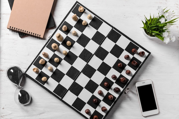 Schachfiguren mit spielbrett und sanduhr auf weißem tisch