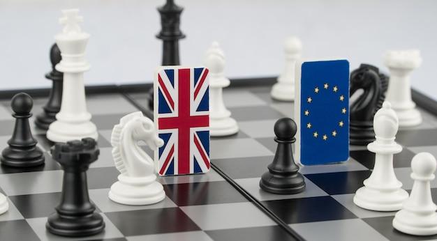 Schachfiguren und flaggen der europäischen union und des vereinigten königreichs auf einem schachbrett politisches spiel