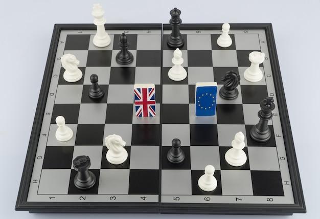 Schachfiguren und flaggen der europäischen union und großbritanniens auf dem schachbrettkonzept des politischen spiels