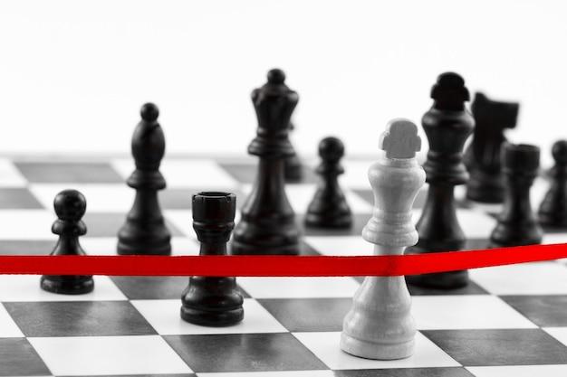 Schachführungskonzept mit königsfigur, die das rote endband überquert. schwarz-weiß-ton