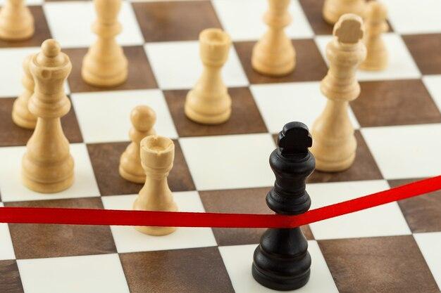 Schachgeschäftskonzept mit königsfigur, die das rote endband überquert