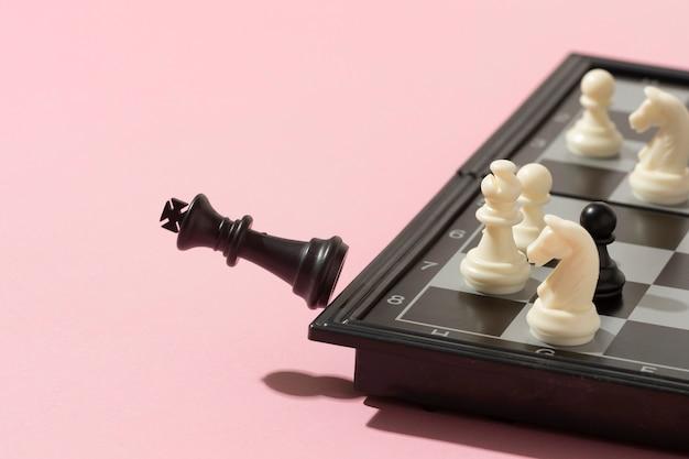 Schachmatt mit schwarzem könig auf rosa hintergrund