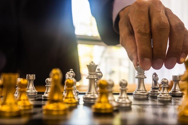 Schachspiel auf schachbrett hinter geschäftsmannhintergrund.