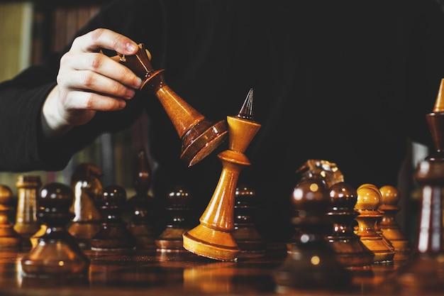 Schachspiel. der typ macht eine bewegung. schachmatt. schachfiguren aus holz. strategiespiel