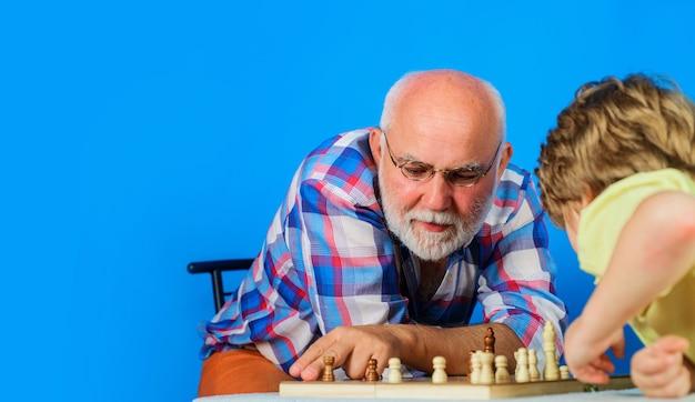Schachspiel. großvater und enkel spielen zusammen schach. familienbeziehung mit opa und enkelkind. platz kopieren.
