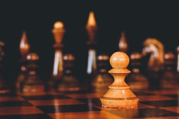 Schachspiel. schachfiguren aus holz. ein bauer auf einem schachtisch. strategiespiel