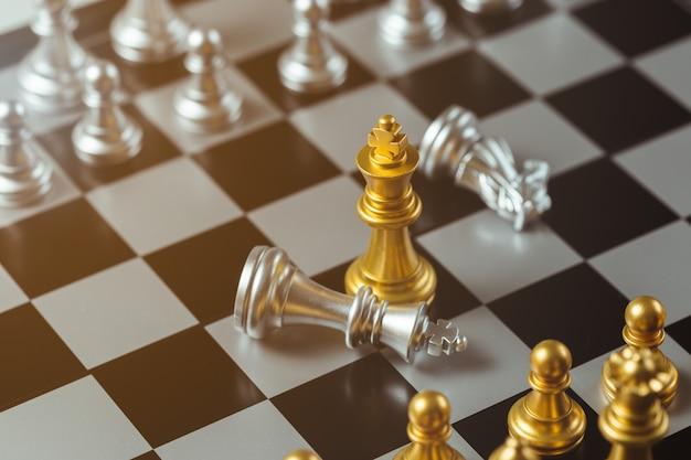 Schachspielgoldkönigstellung und silbernes schachbrett, geschäftsstrategiekonzept.