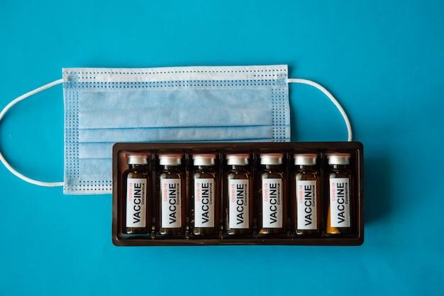 Schachtel ampullen mit etikett und medizinischer maske auf blauem hintergrund mit kopienraum, nahaufnahme.
