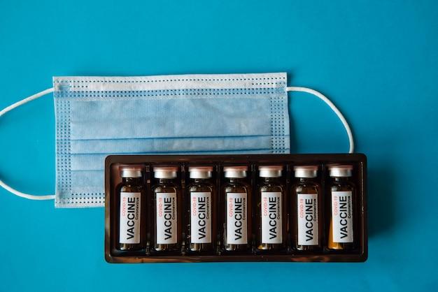 Schachtel ampullen mit etikett und medizinischer maske auf blauer oberfläche mit kopierraum, nahaufnahme. coronavirus-impfstoff gebrauchsfertig. massenimpfung der bevölkerung.
