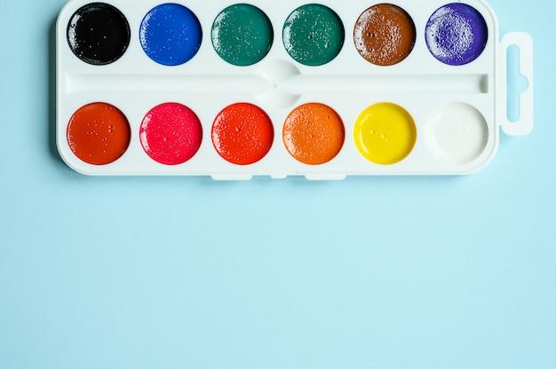 Schachtel aquarellfarben auf blauem hintergrund