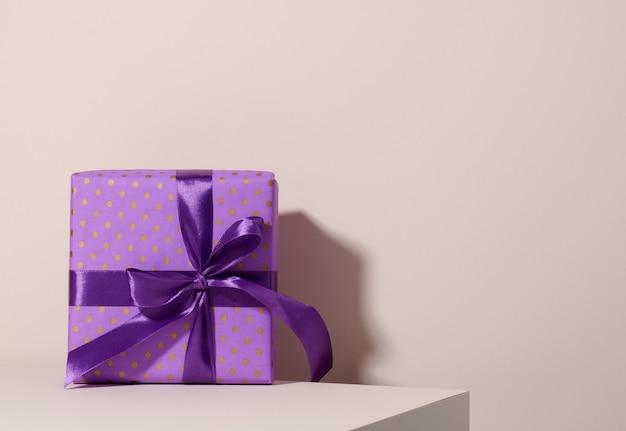 Schachtel in festlichem lila papier verpackt und mit seidenband auf beigem hintergrund gebunden, geburtstagsgeschenk, überraschung