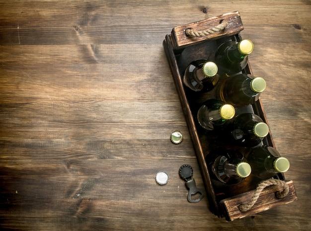 Schachtel mit frischem bier auf holztisch.