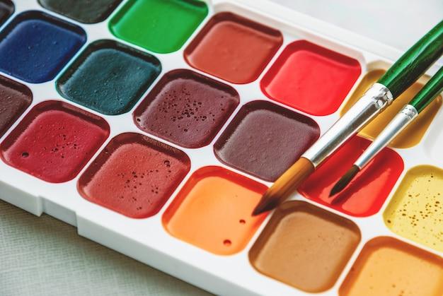 Schachtel mit neuen aquarellfarben und nahaufnahme mit zwei pinseln