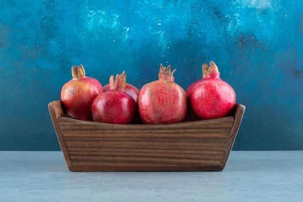 Schachtel mit reifen granatäpfeln auf marmor.