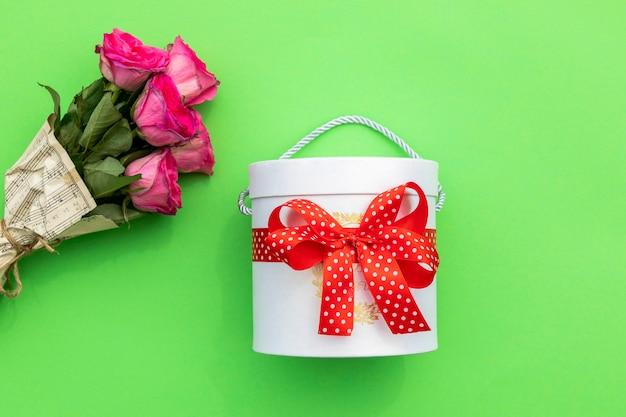 Schachtel mit süßigkeiten und rosenstrauss