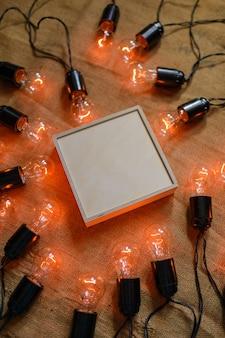 Schachtel sperrholz umgeben von retro-girlande mit edison-lampen